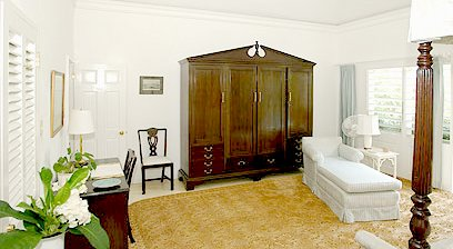 The Master Bedroom is distinguished by an 18th Century-style mahogany armoire that houses a flat screen television.