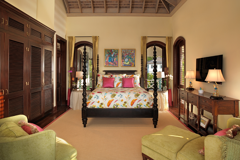 With elegant four-poster bed and fabrics in tropical shades of coral and green ...