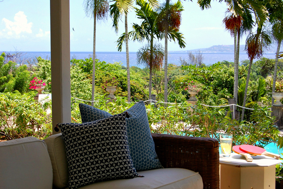 The living room opens wide to the covered verandah, furnished with Queen Anne dining table, wicker seating and