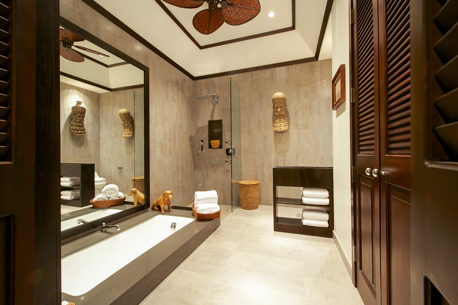 ... has a deep bathtub and large open Travertine-tiled shower.