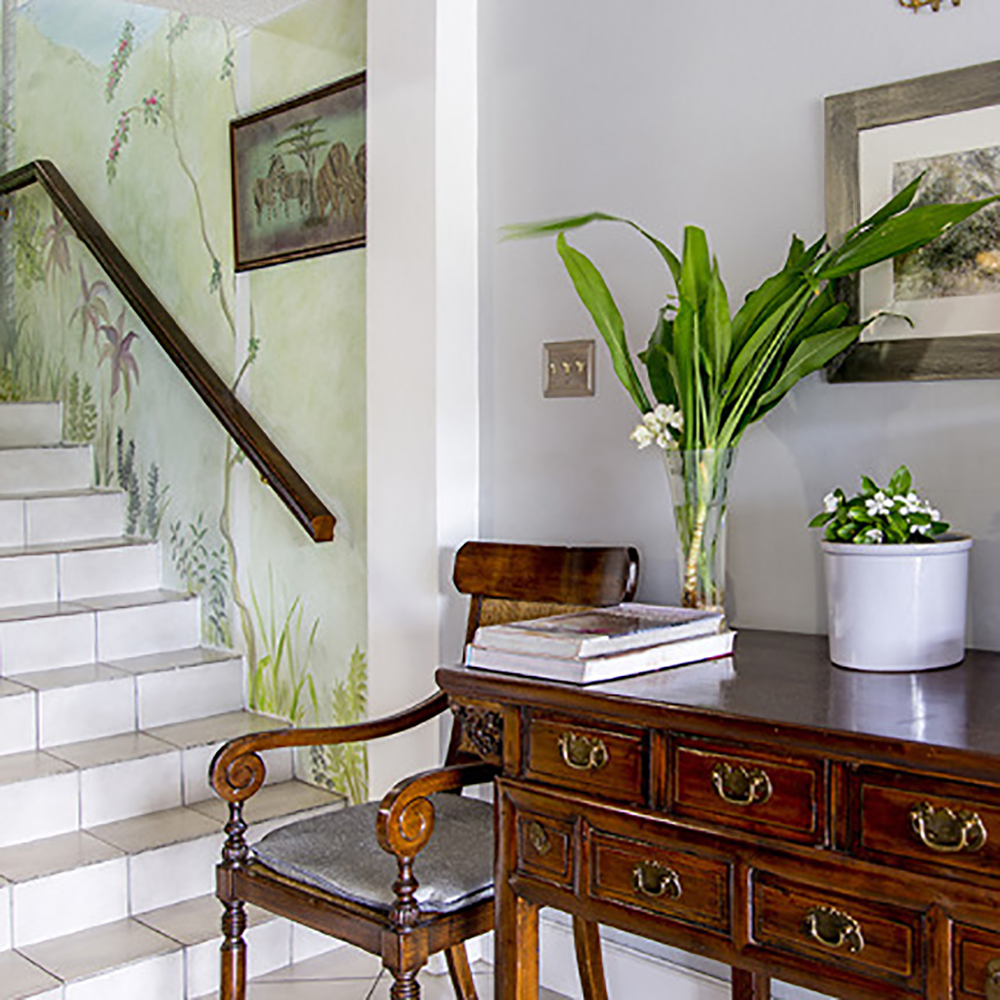 GOING UPSTAIRS A custom-painted mural lines the walls leading up to the very private master suite, one floor above.
