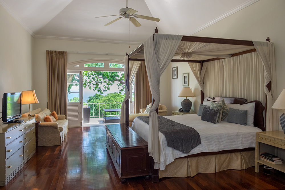 Master bedroom with king-size, four poster bed.