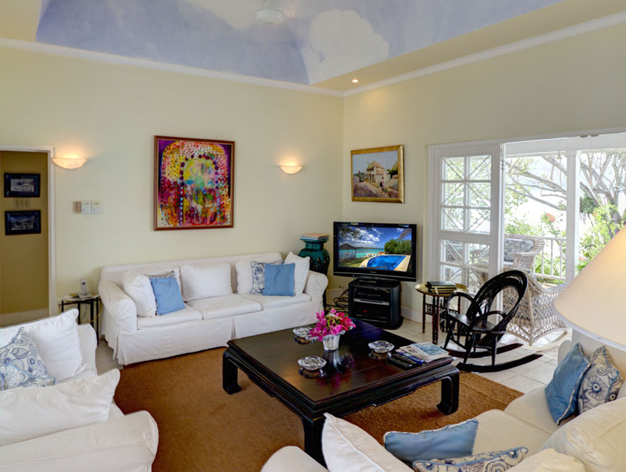 The living room is sunshine yellow with a vaulted ceiling painted to match the sky. Antiques include a 200-year-old rocker made of twigs.