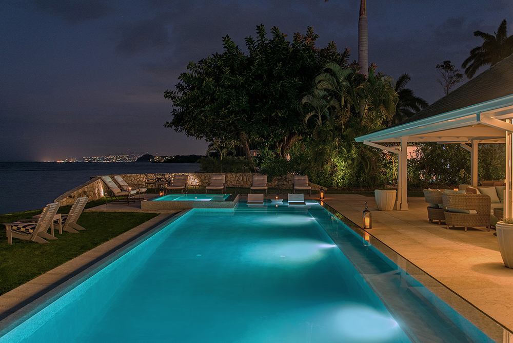 Pool at night with lights from Montego Bay in the distance.