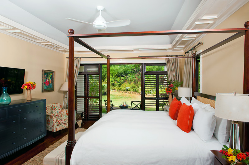 Adjacent BEDROOM 5 has a 4-poster king bed and en-suite bathroom with deep tub and glass shower. The bedroom  wall opens  to a patio and lawn a few feet from the pool terrace.