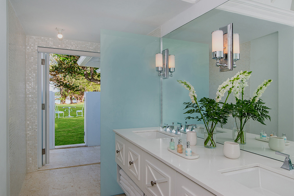 Its bathroom provides a double vanity, inside and outside showers and opens to the side lawn.