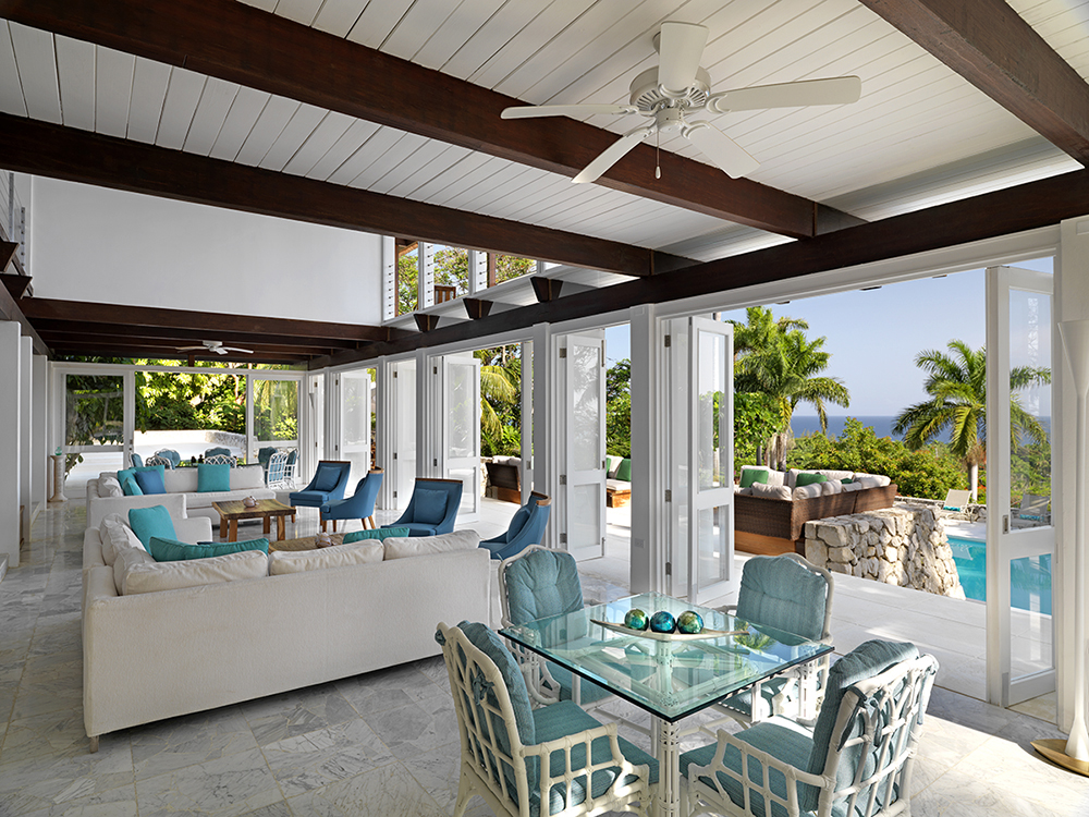 Expansive folding doors open from the main floor lounge area ... where crisp blue and white fabrics emulate the colors of the pool, sea and sky beyond.