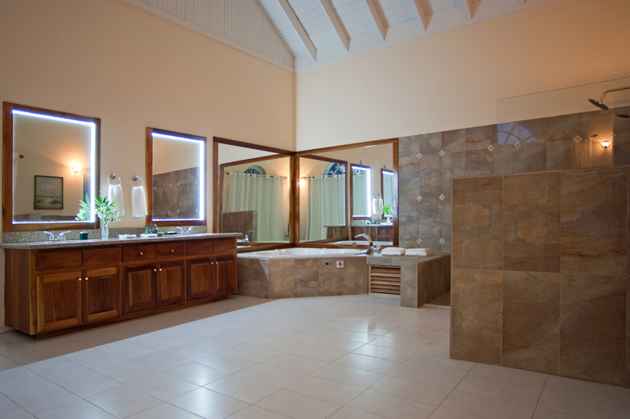 ... a glamorous new bathroom with Jacuzzi tub for two as well as a large, open Travertine shower.  A wide window wall provides vast views over the grounds and sea.